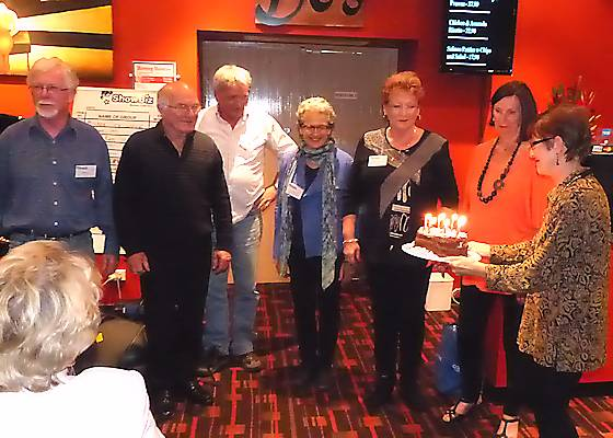 October birthday crowd; from L: John Curtis, Colin Garrett, Gary Russell, Marion Lustig, Renée Rundell and Judy Forbes, served by faultless cake manipulator Janet Arndt.